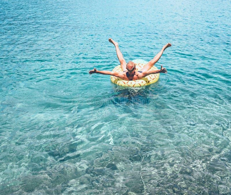 Человек ослабляя когда заплывы на раздувном кольце бассейна ананаса в кристально ясной морской воде Халатное изображение концепци стоковое фото rf