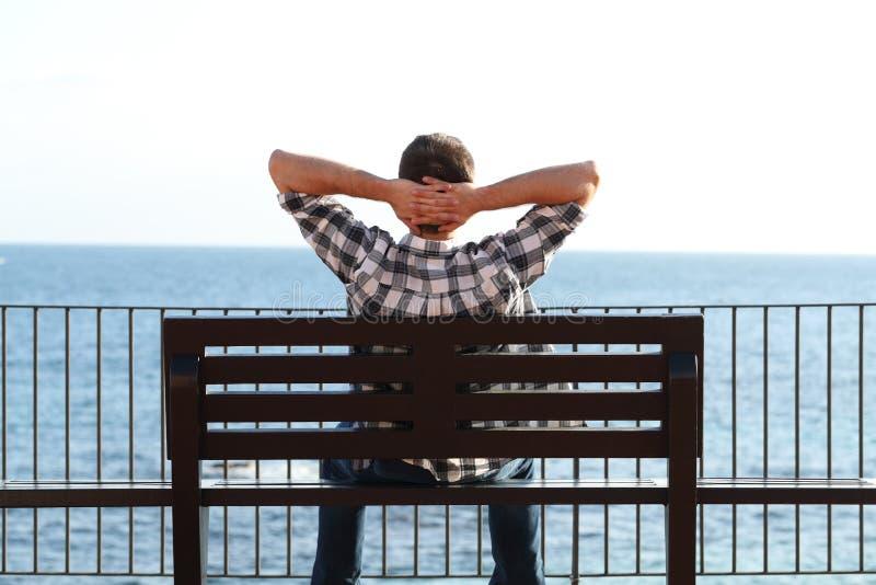 Человек ослабляя на пляже сидя на стенде стоковые изображения