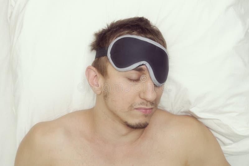 Человек отдыхая в маске для сна Стерня на его стороне утомлянный человек стоковые изображения