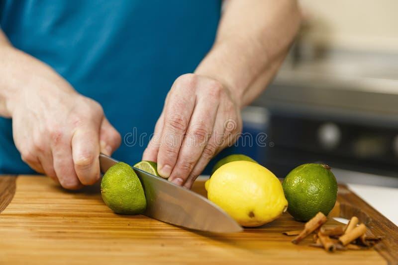 Человек отрезая известки и лимоны стоковое фото