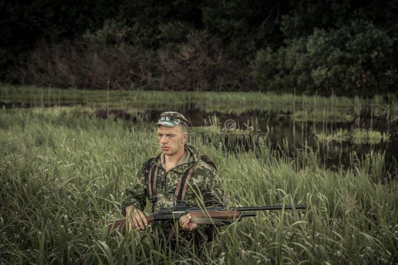 Человек охотника звероловства зверский выходить трава болота высокорослая во время сезона звероловства стоковая фотография