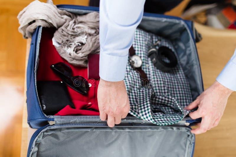 Человек пакуя его одежды и вещество стоковые фото
