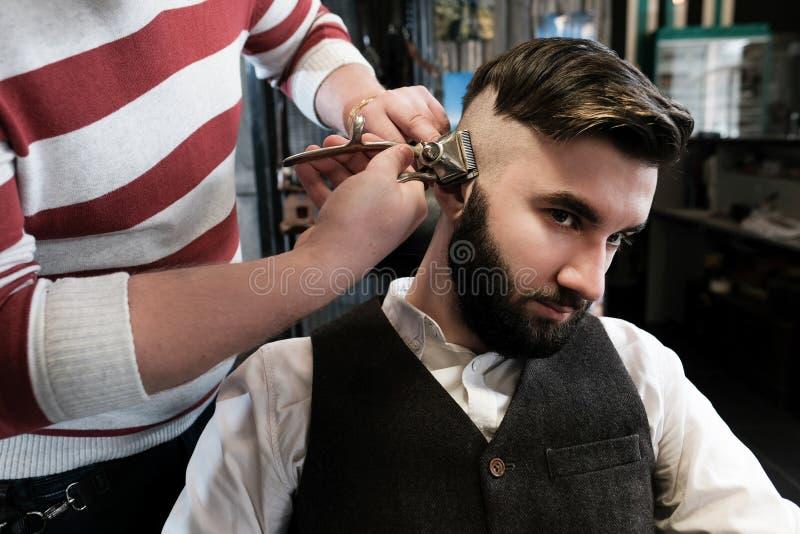 Человек парикмахера бреет клиента с бородой в парикмахерскае стоковая фотография
