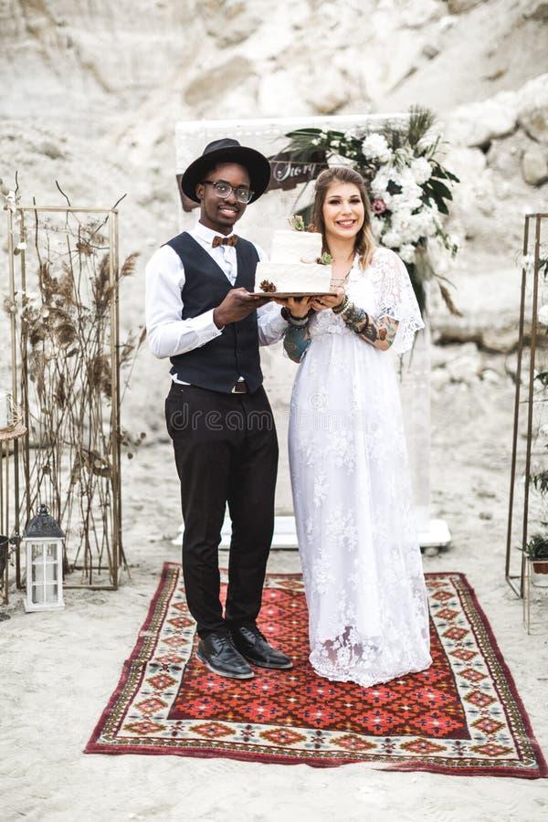 Человек пар африканский и кавказская женщина в их одеждах свадьбы boho держа белый торт украшенный с succulents стоковое фото rf