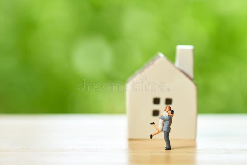 2 человек пар миниатюрное стоя модельно с моделью дома делает f стоковое фото