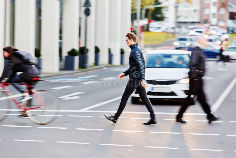 Человек пересекает улицу города стоковая фотография