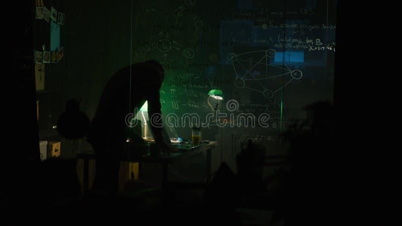 Человек пишет на стеклянной доске на ноче шток Неузнаваемый гений самостоятельно пишет вниз формулы на классн классном стоковая фотография