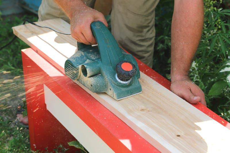Человек плотника кладет деревянную планку против электрического pla стоковое фото rf