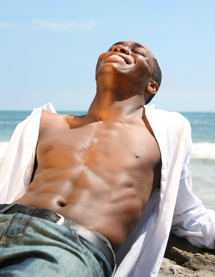 человек пляжа смеясь над outdoors представляя стоковое изображение
