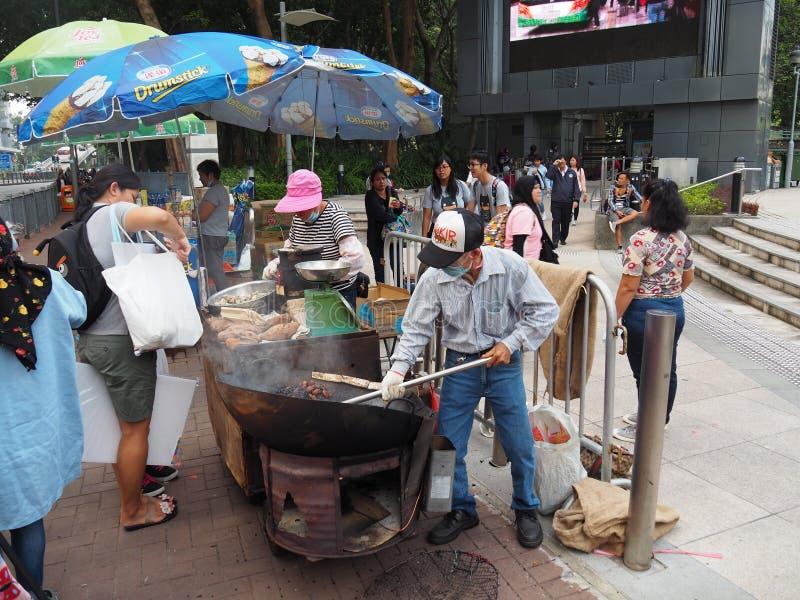 Человек подготавливает еду улицы в Гонконге стоковые изображения rf