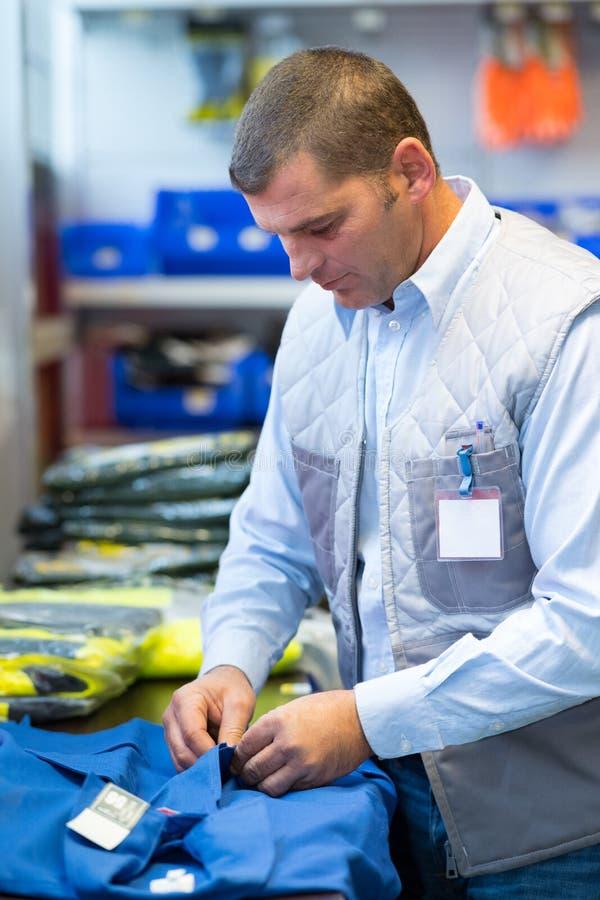Человек подготавливая прозодежды работы заказа стоковые фотографии rf