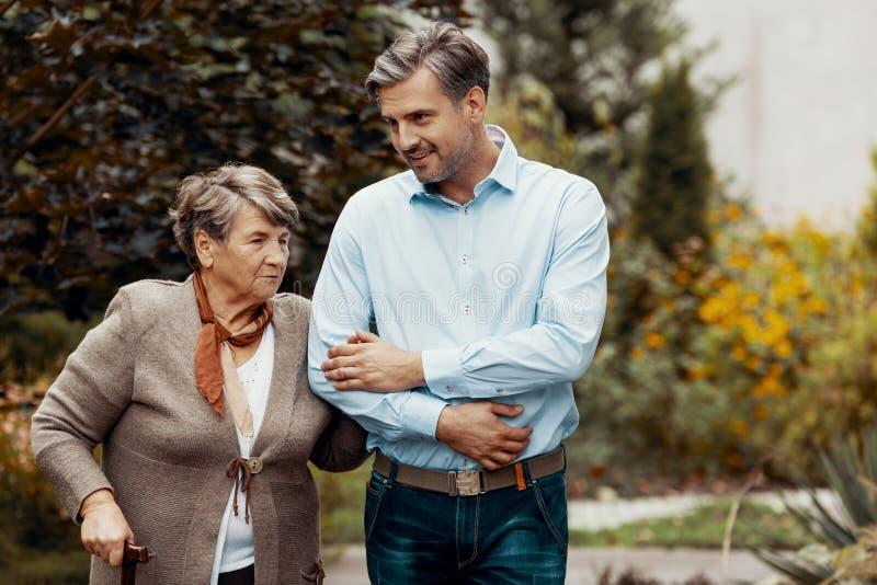 Человек поддерживая старшую женщину пока идущ в сад стоковое фото rf