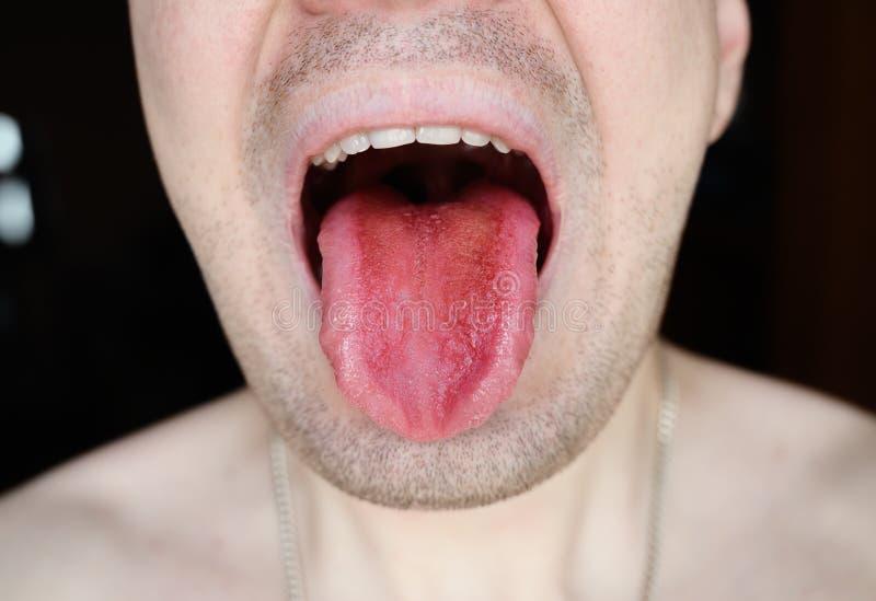 Человек показывает его язык стоковые изображения