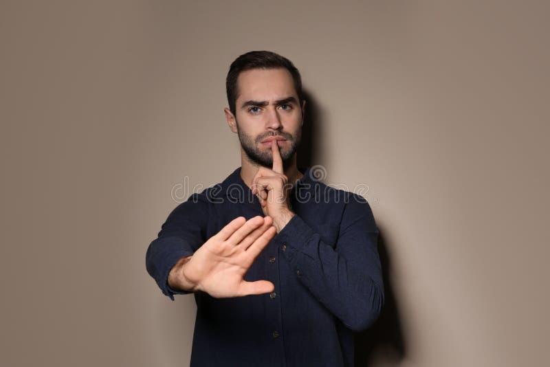 Человек показывая жест HUSH в языке жестов на предпосылке стоковые изображения rf