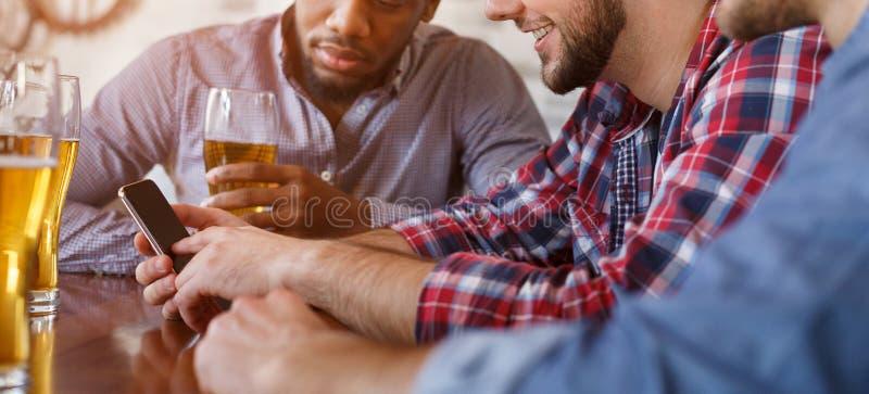 Человек показывая новое приложение на смартфоне, отдыхая в Адвокатуре с друзьями стоковые фото