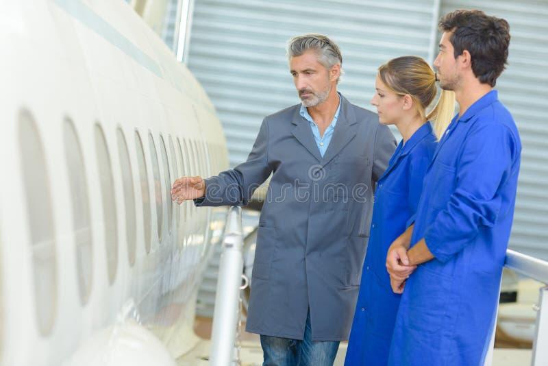 Человек показывая фюзеляж воздушных судн к студентам стоковое фото