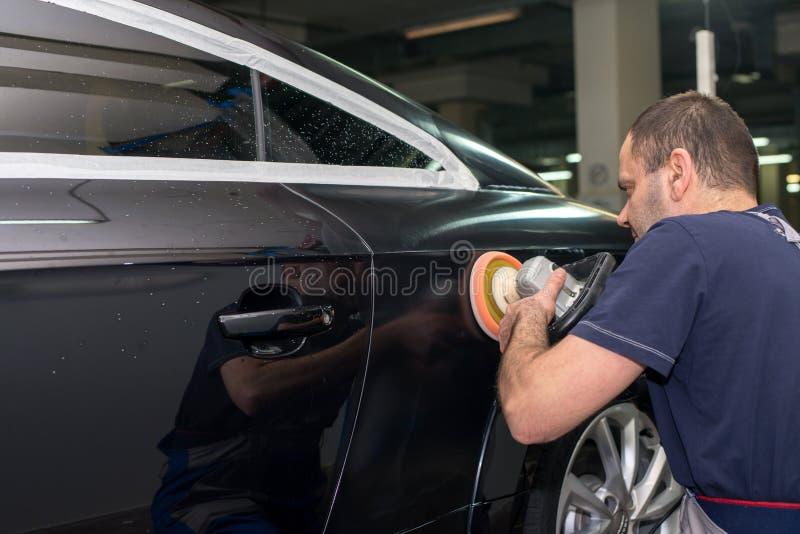 Человек полирует черный автомобиль стоковые изображения