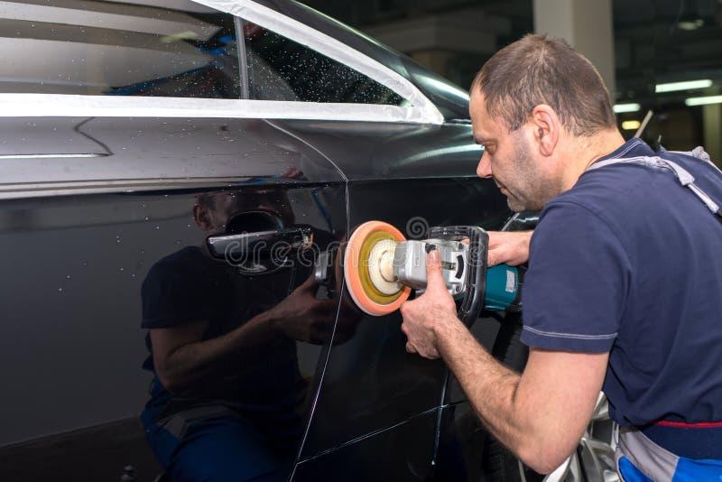 Человек полирует черный автомобиль стоковые фотографии rf