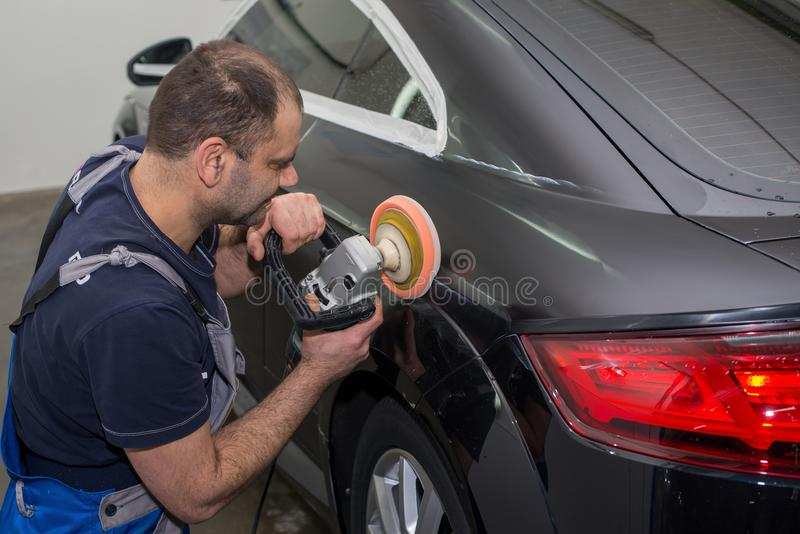 Человек полирует черный автомобиль стоковая фотография rf