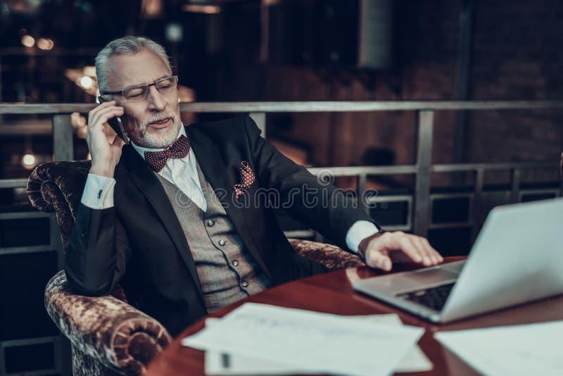 Человек положился назад в стуле и говорить на телефоне стоковые фото