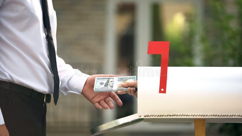 Человек, получающий доллары от почтового ящика, с помощью службы трансфертов, финансовых операций стоковые фото