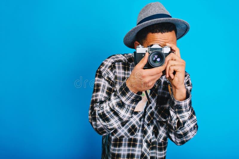 Человек портрета стильный молодой в шляпе делая фото на камере на голубой предпосылке Tavelling, выходные, праздники, возбужденны стоковое изображение rf