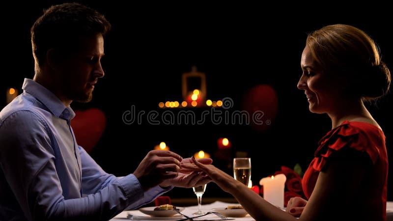 Человек предлагая к любимой даме, кладя драгоценное кольцо на палец, романтичный обедающий стоковое фото
