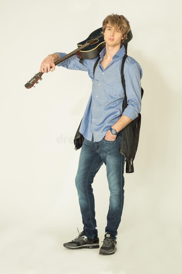 Человек представляя дальше с гитарой на светлой предпосылке стоковое изображение rf