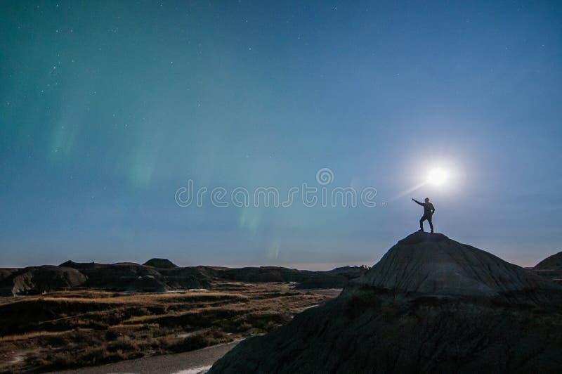 Человек представляя против ночного неба стоковое изображение