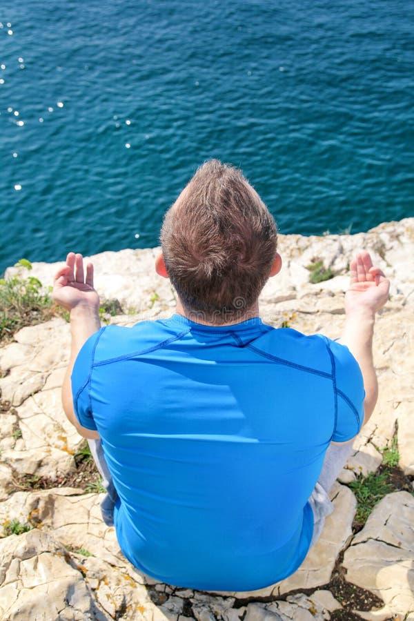 Человек пригонки в положении лотоса на seashore Молодой человек фитнеса делая йогу outdoors стоковые изображения