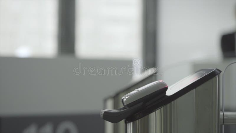 Человек прикладывая браслет RFID к электронному оборудованию доступа на въездных воротах к метро, подполью или спортзалу Рамка стоковая фотография