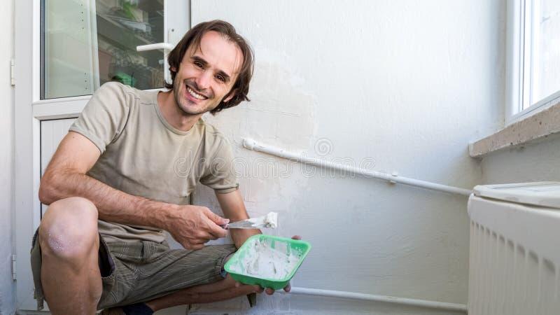Человек прикладывая смешивание гипсолита на стене со шпателем Легкая домашняя восстанавливая концепция стоковые фотографии rf