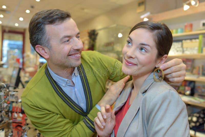 Человек прикрепляя ожерелье в шею девушек в магазине розничной торговли стоковые фотографии rf