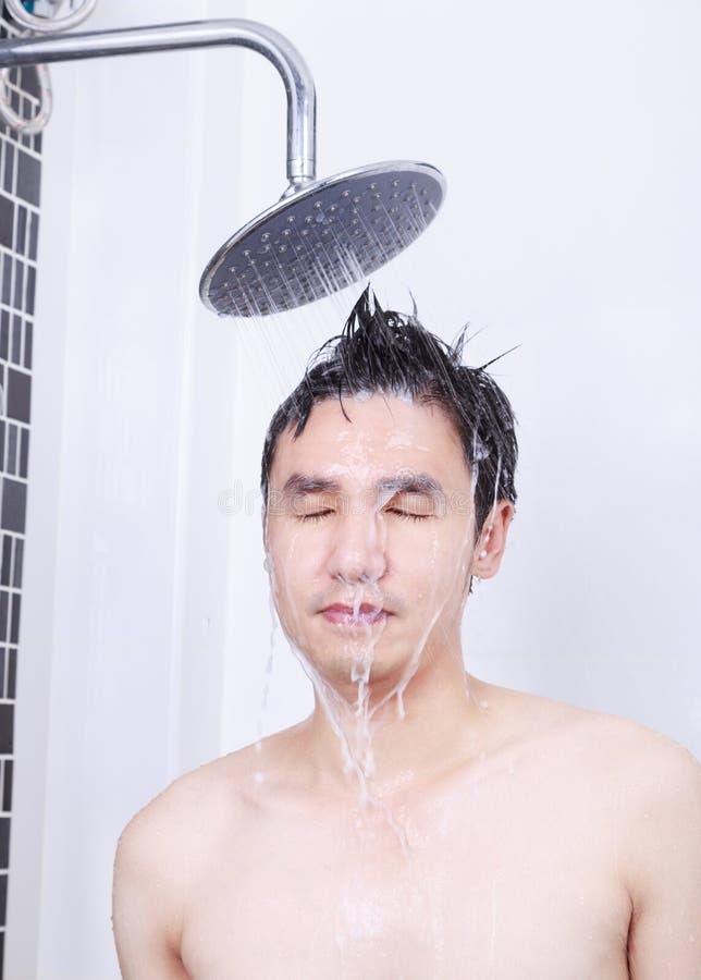 Человек принимает дождь и моя волосы в ванной комнате стоковое изображение rf