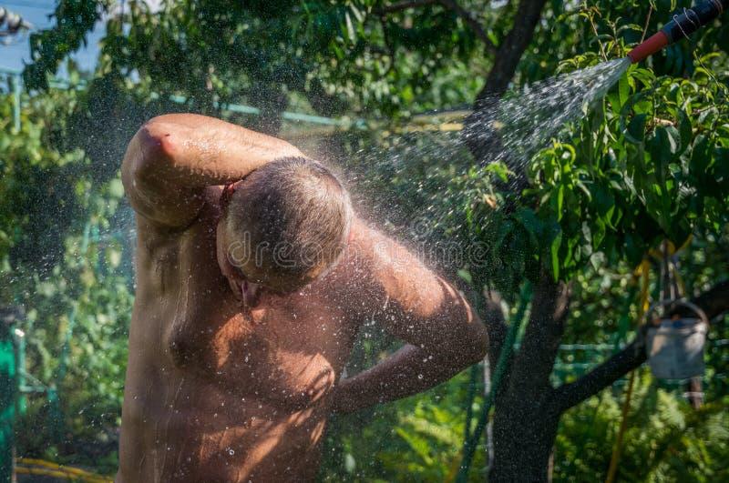 Человек принимает ливень на лужайке в саде стоковые фото