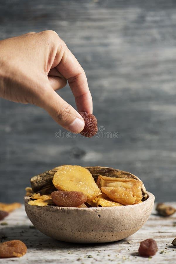 Человек принимая высушенную клубнику стоковая фотография