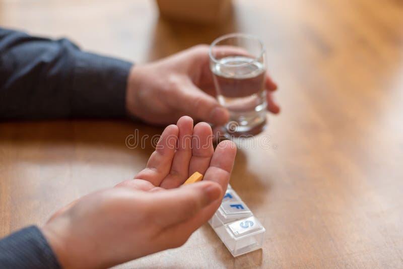 Человек принимая ежедневные витамины для хороших здоровий стоковое изображение