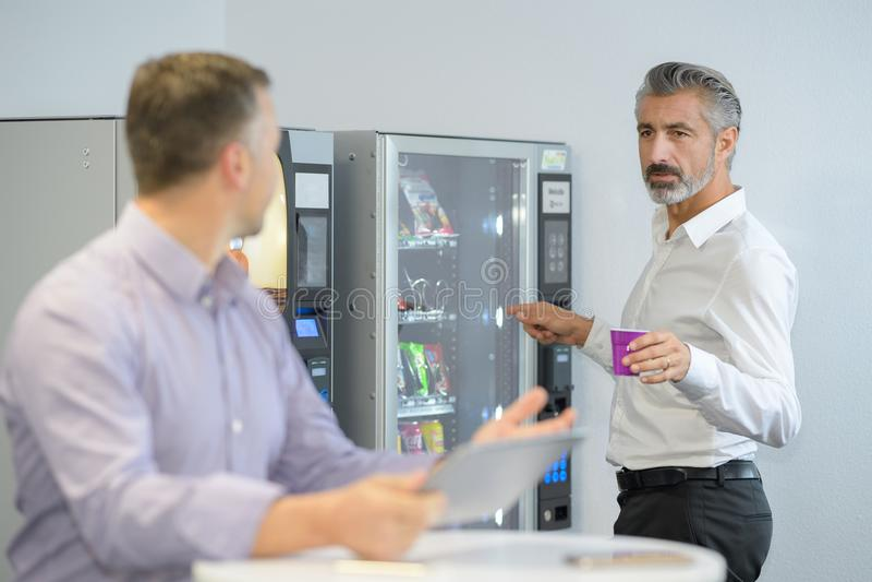 Человек принимая кофе от торгового автомата стоковое фото