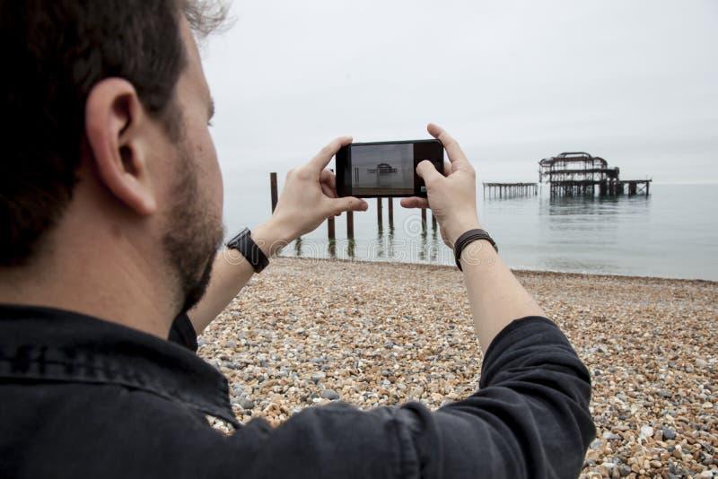 Человек принимая фото в море стоковая фотография rf
