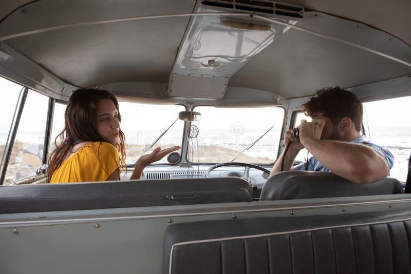 Человек принимая фото женщины с цифровой фотокамерой в жилом фургоне стоковые фото