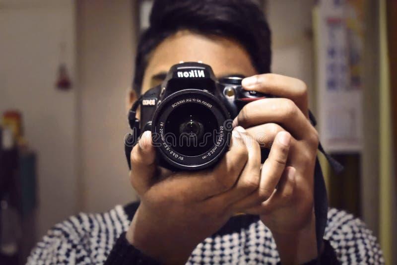 Человек принимая фото от его камеры Nikon DSLR смотря на камеру стоковые изображения rf