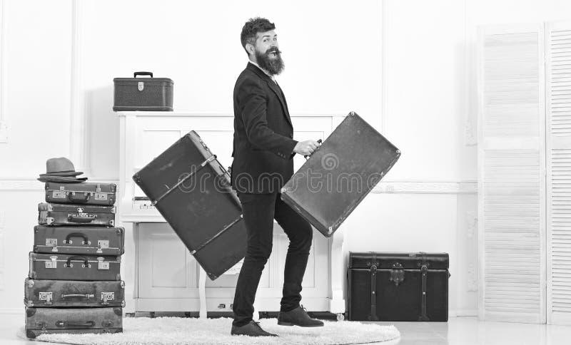 Человек при борода и усик нося классический костюм поставляет багаж, роскошную белую внутреннюю предпосылку Мачо привлекательное стоковое фото rf