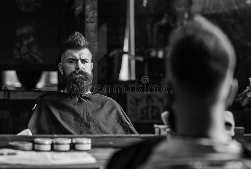 Человек при борода покрытая с черной накидкой сидит в стуле парикмахеров перед зеркалом Битник с бородой проверяя результат стоковые изображения rf