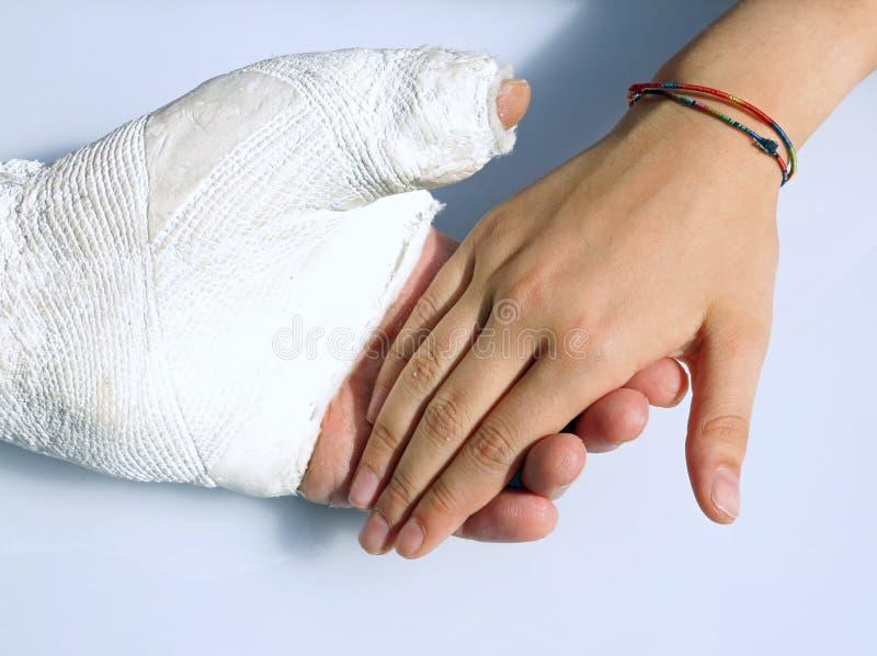 Человек при его заштукатуренная рука держит руку его дочери стоковые фото