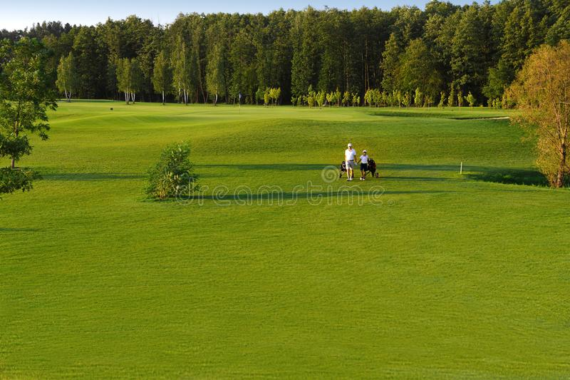 Человек при его игроки в гольф сына идя на поле для гольфа стоковые фото