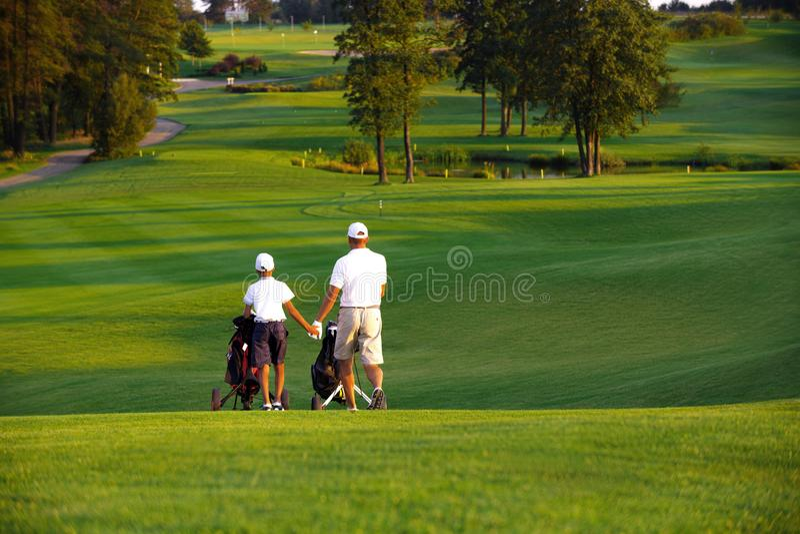 Человек при его игроки в гольф сына идя на поле для гольфа стоковое изображение