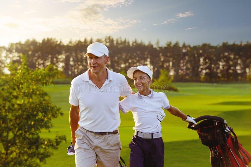 Человек при его игроки в гольф сына идя на поле для гольфа стоковые изображения rf