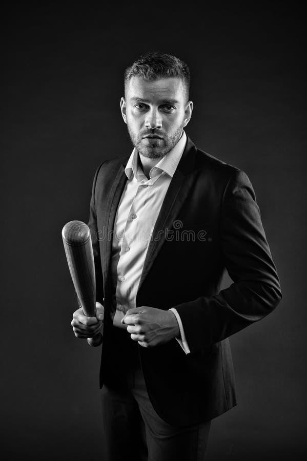 Человек при зверская сторона держа бейсбольную биту Гай в костюме изолированном на черной предпосылке Боец с уверенно взглядом ра стоковые фото