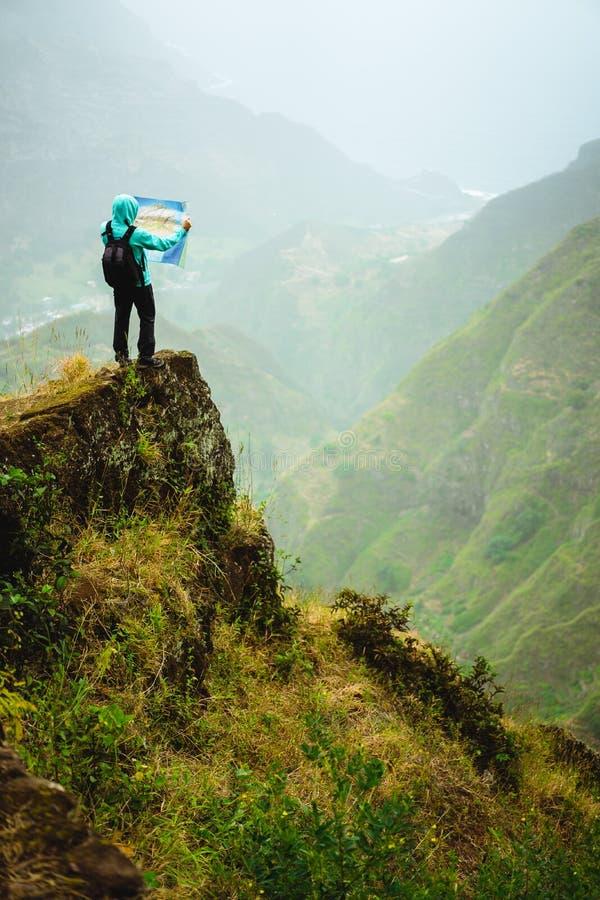 Человек при карта оставаясь na górze утеса перед шикарным взглядом панорамы высоких горных цепей и сочного зеленого цвета стоковое фото rf