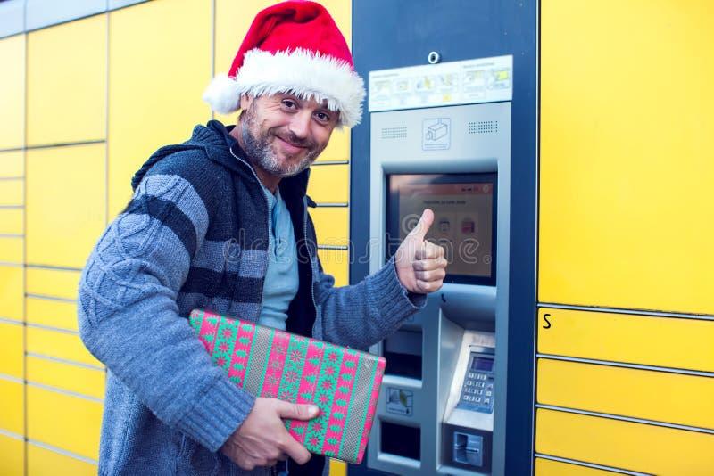 Человек при клиент шляпы santa используя автоматизированное условие столба обслуживания собственной личности стоковое изображение